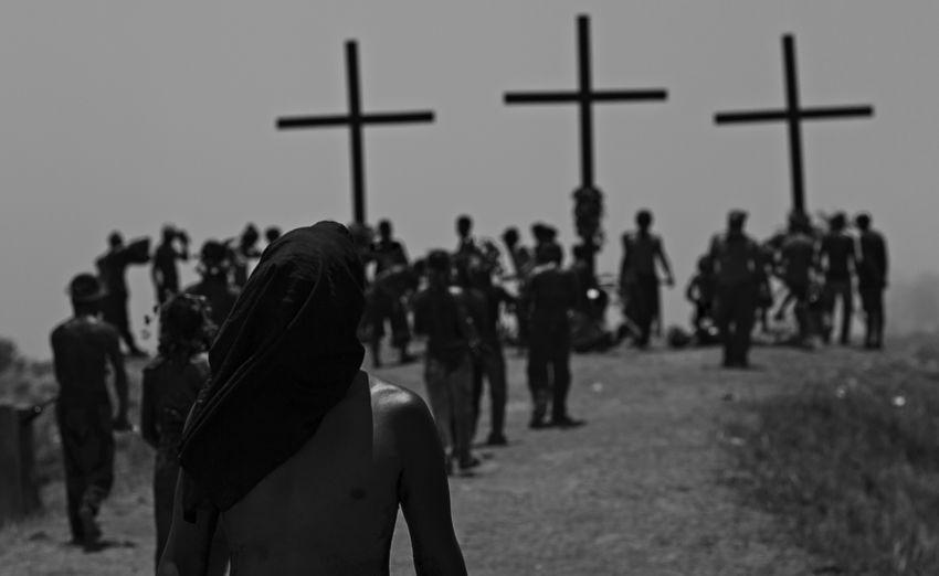 People by cross against sky