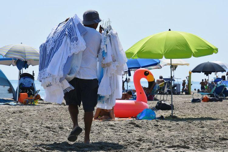 People Vendor Men Beach Full Length Togetherness Sand Women Walking Summer Sky Beach Umbrella Parasol