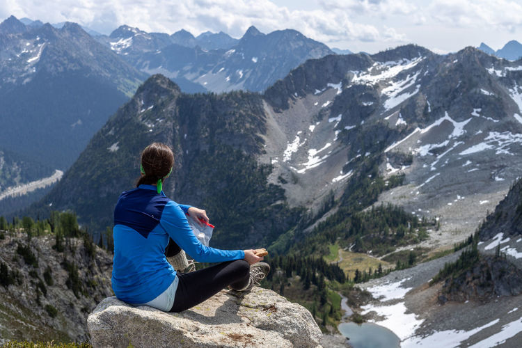 Man sitting on rock looking at mountains