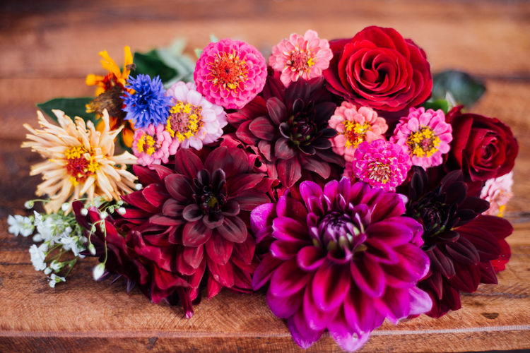 High angle view of various flowers arranged on wooden table