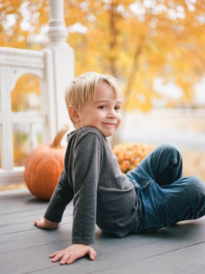Portrait of cute boy sitting against building
