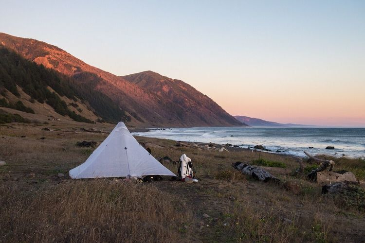 Tent on beach by mountains against clear sky during sunset