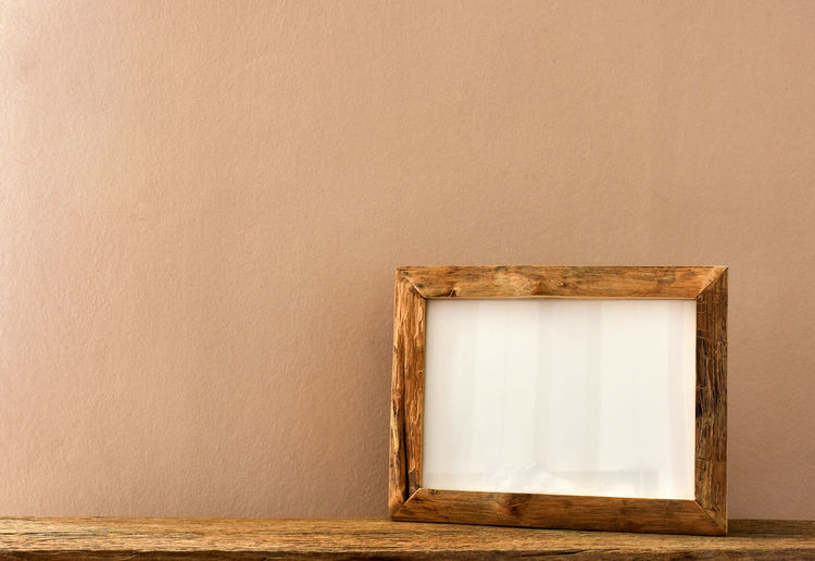 Empty wooden picture frame against the wall background.