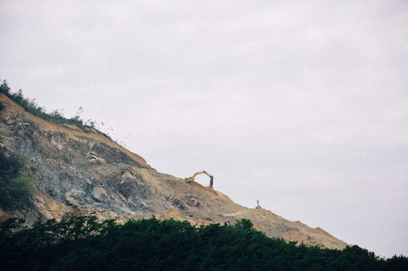Distant Image Of Construction Excavator On Mountain Against Sky