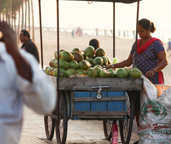 COCONUTS SELLER ON THE BEACH SIDE Coconuts Fruit Women Healthy Lifestyle Young Women Market Human Hand City Happiness Market Vendor Vendor Stall For Sale Selling Display Street Market International Women's Day 2019 Streetwise Photography