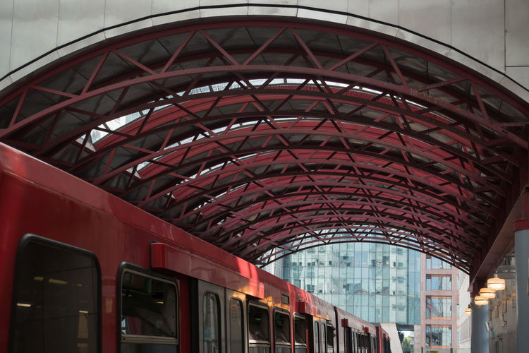 The Red Roof Canary Wharf DLR Docklands Light Railway Arch Arched Roof Architecture Built Structure City Connection Day Glass - Material Land Vehicle Low Angle View Mode Of Transportation No People Outdoors Passenger Train Public Transportation Rail Transportation Railroad Station Red Train Train - Vehicle Transportation Travel
