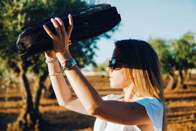 Side view of woman shielding eyes while standing at olive orchard