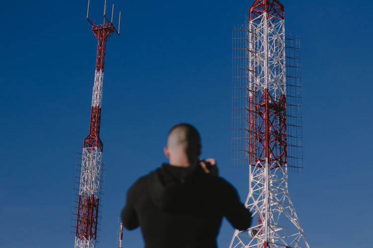 Man Standing Against Communications Tower