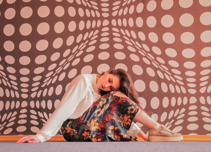 Side view of woman sitting on floor against patterned wall