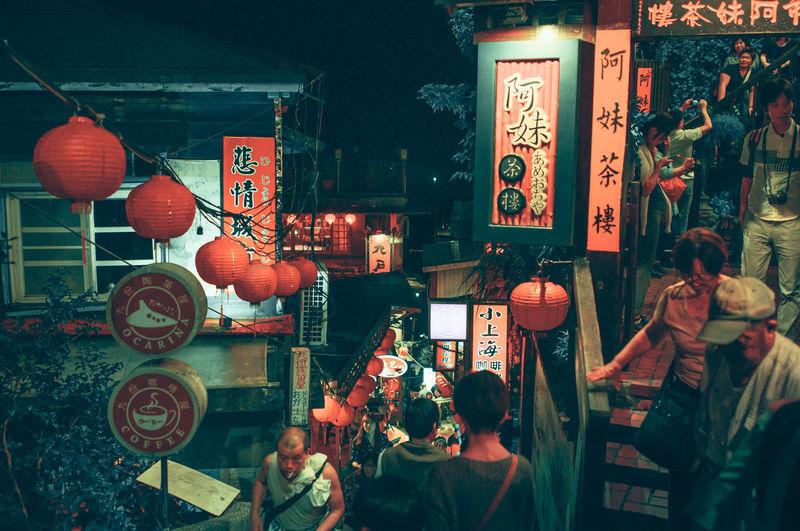 Illuminated lanterns hanging at market in city at night