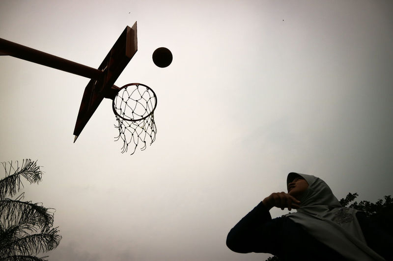 Low Angle View Of Woman Playing Basketball Against Sky