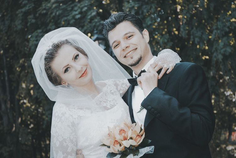 Portrait of happy young bride and groom standing against trees