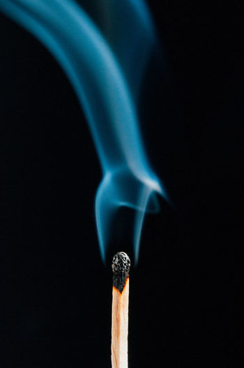 Close-up of burnt matchstick with smoke against black background