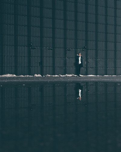 Man standing at lake against wall