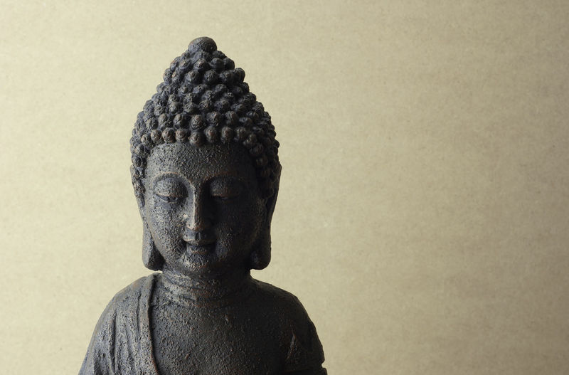 Close-up of buddha statue against wall