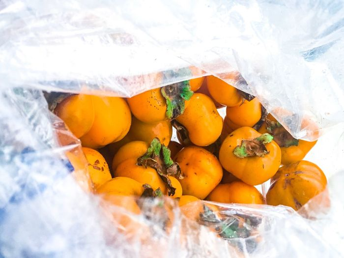 Close-up of persimmons in plastic for sale at market stall