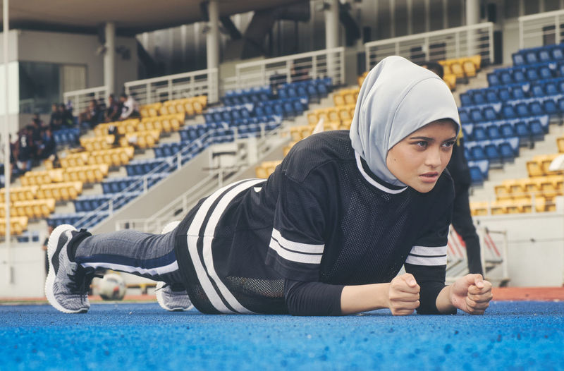 Sportswoman stretching and having some warming up before running One Person Real People Front View Sport Seat Headscarf Clothing Sitting Young Adult Day Hijab Full Length Focus On Foreground Cap Lifestyles Casual Clothing Indoors  Young Women