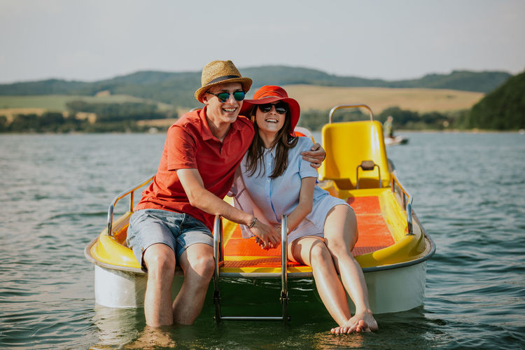 Front view of smiling young couple sitting on pedal boat. Portrait of man and woman in love enjoying boating on the lake. Boating Couple Holiday Hot Day Love Summertime Vacations Young Boat Boyfriend Caucasian Feet Girlfriend Lake Outdoors Pedalo Relax Resting River Sea Summer Sunglasses Sunhat Two People Water