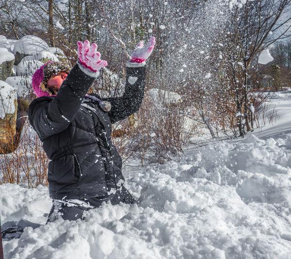 View of girl flinging snow