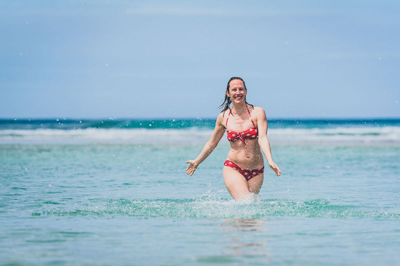 Portrait of happy mid adult woman in sea against sky