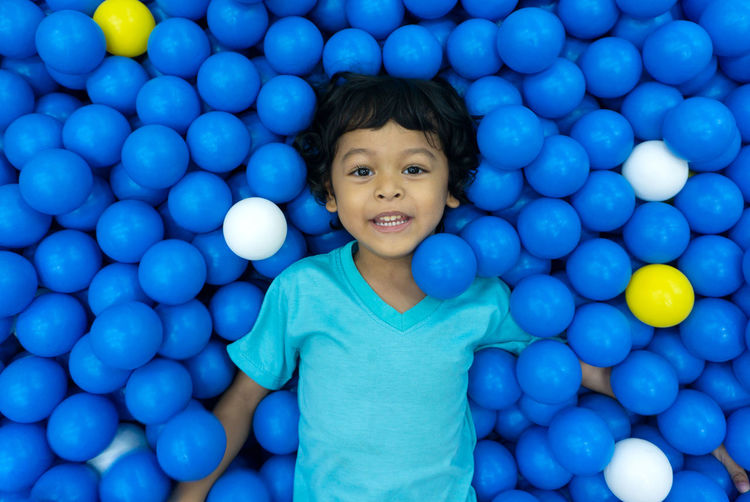 A little Asian boy is playing with a lot of blue and yellow balls. And eyes looking at the camera With a happy smile. Fun Child Childhood Ball Play Game Happy Background Kid Colorful Boy Leisure Active Little Activity Cute Sport Pool Happiness Joy People Young Playful Playground Kids Soccer Football Together Smile Male Party Girl Holiday Children Balls Smiling Plastic Toy Playing Cheerful Color Green Many Red Entertainment Caucasian Lifestyle person Small White