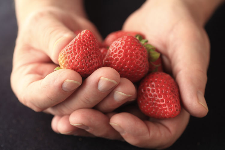 Cropped image of person holding strawberries on table