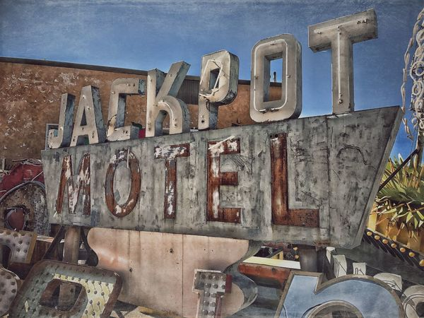 At the Neon Boneyard. Neon Old Neon Sign Old Neon Neon Boneyard Motel Motel Sign Old Motel Sign Faded Faded Color Faded Beauty Jackpot Junkyard The Week Of Eyeem Green Rust Color Rust Rusted Metal  Multi Colored Abanoned Metal Text Communication No People Day Close-up Outdoors Sky Women Around The World