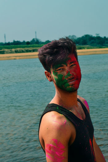 Portrait of man covered with powder paint at riverbank during holi against sky