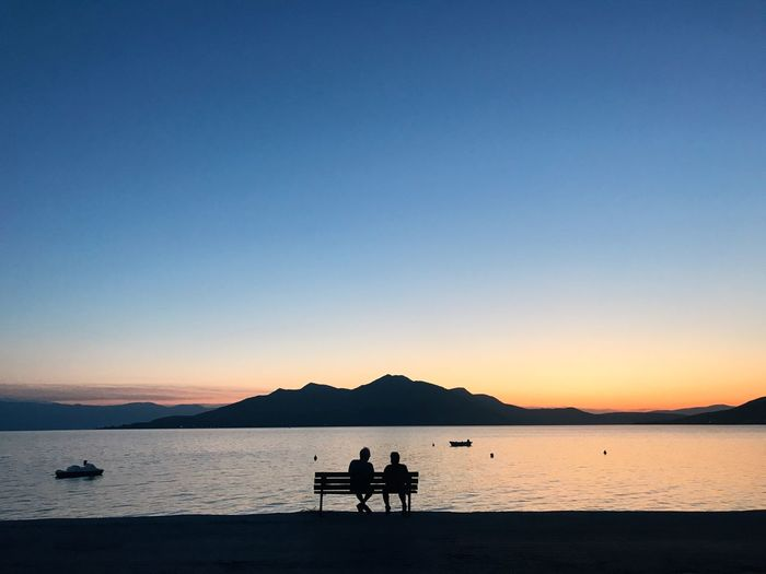 Silhouette people sitting on bench by lake against sky during sunset