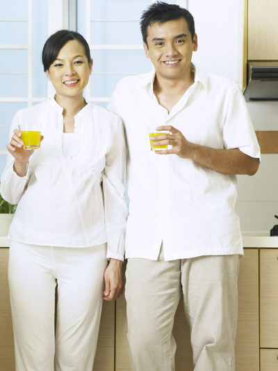 Portrait of couple having drink while standing at home