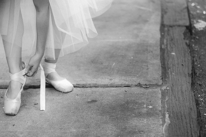Low section of woman wearing ballet shoes on sidewalk