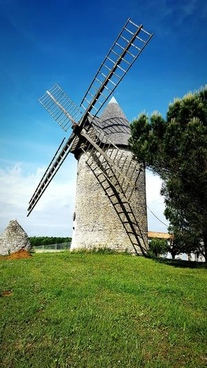 Windmill Somehere In France Blue Renewable Energy Fuel And Power Generation Rural Scene Environmental Conservation Grass Architecture Alternative Energy Tree Wind Power Sky Tall Growth Day Green Color Outdoors Green No People Grassland Blue Renewable Energy Fuel And Power Generation