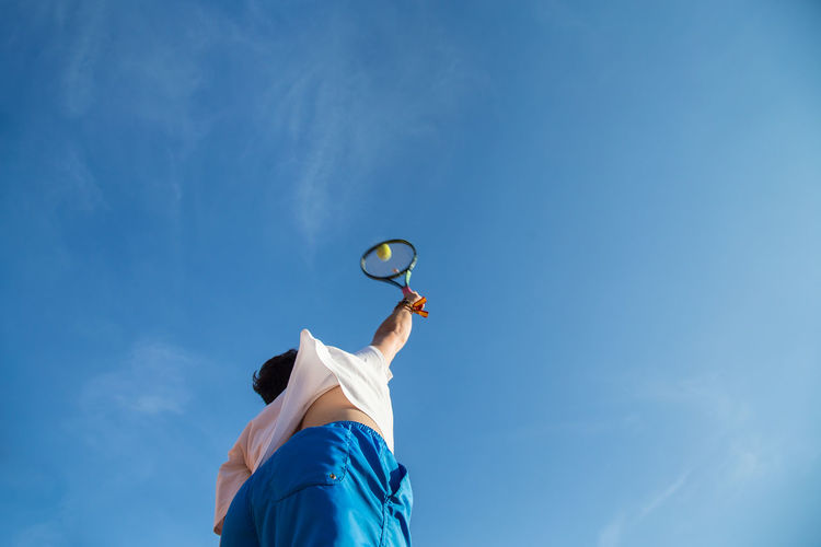 Low Angle View Of Man Playing Tennis Against Blue Sky