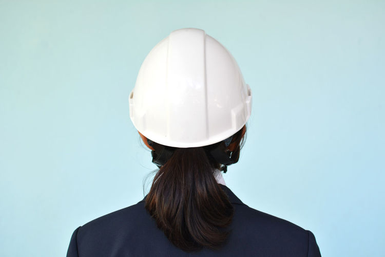 Rear view of businesswoman wearing hardhat against blue background