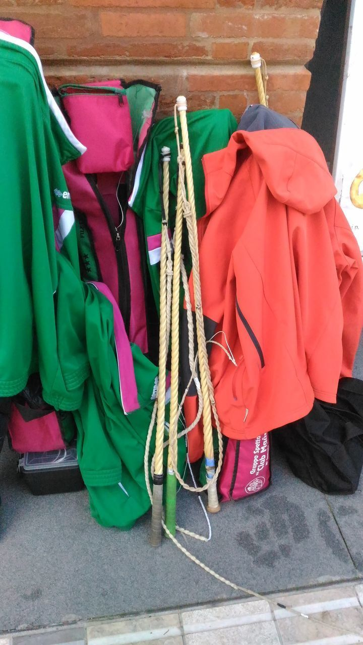 hanging, day, no people, choice, variation, clothing, large group of objects, green color, outdoors, multi colored, retail, close-up, coathanger, rack, abundance, side by side, red, store, bag, clothes rack