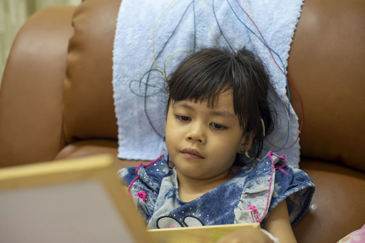 Close-up of cute girl with electrodes on head sitting on sofa at home