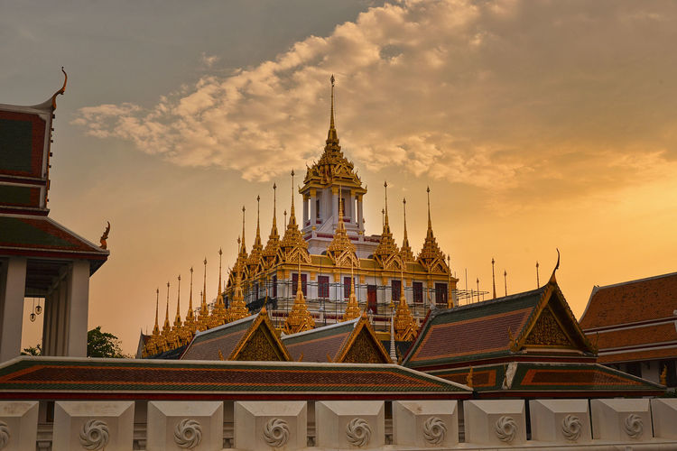 tropical swimming pool at night and Buddhist Temple in thailand Architecture Built Structure Building Exterior Sky Building Travel Destinations Cloud - Sky Place Of Worship Belief City No People Religion Nature Sunset Spirituality Travel Tourism Tower Low Angle View Spire  Outdoors Ornate