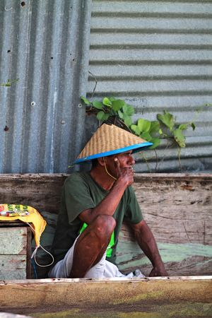 Adult Adults Only Corrugated Iron Day Food Freshness Holding Leaf Men Nelayan Occupation One Person Outdoors People Plant Real People Sitting Working Sitting Adult Human Body Part Working Farmer Social Issues