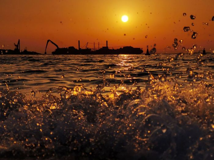 Construction site on the sea Industry Not Sustainable Dubai Cityscape Sunlight Reflection Concrete Jungle Evening Dubai Sunsets Sunset Silhouettes Construction Wave Breaking Waves Crushing Waves Crushing Beach Destroying The Planet Destroying GREED More More More! Water Sunset Wave City Silhouette Sea Sun Gold Colored Seascape Tide Coast