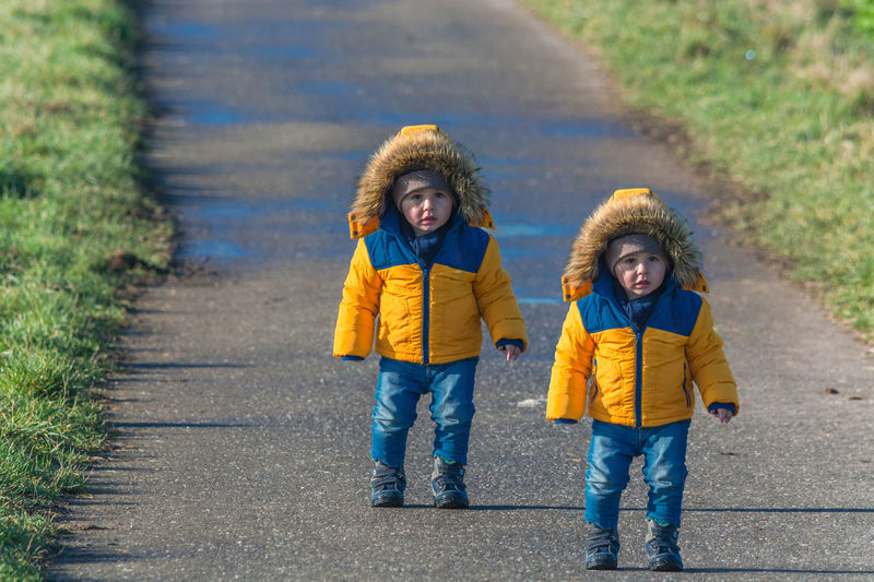 Portrait of twin brothers wearing warm clothing while standing on road