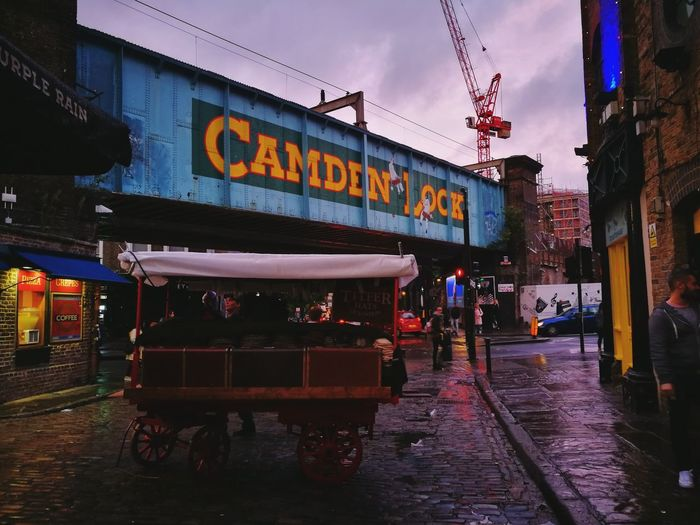 Camden Market after rain during sunset. Text Western Script Architecture Outdoors Travel Destinations Day No People Building Exterior City Sky Camden TownOne Person Camdenmarket London Uk Camden Lock Camden People Transportation Sunsets
