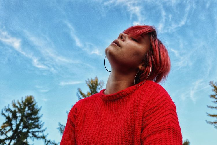 Low angle of young woman standing against sky