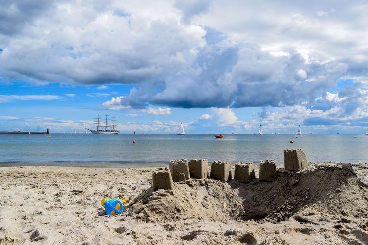 Sandcastles at beach against cloudy sky