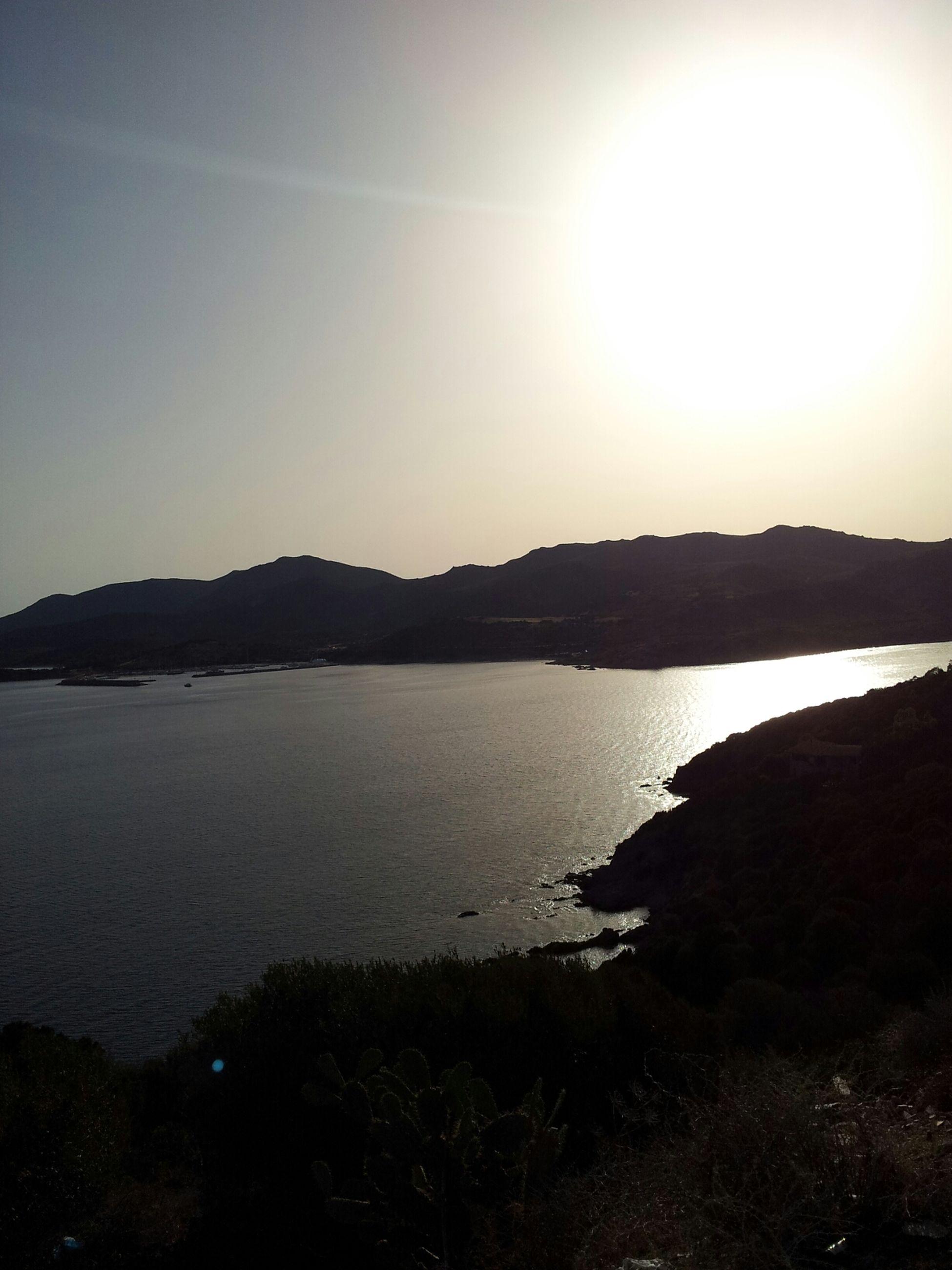 water, tranquil scene, tranquility, scenics, beauty in nature, mountain, sun, reflection, sea, nature, sunset, silhouette, sky, lake, sunlight, idyllic, shore, beach, calm, mountain range