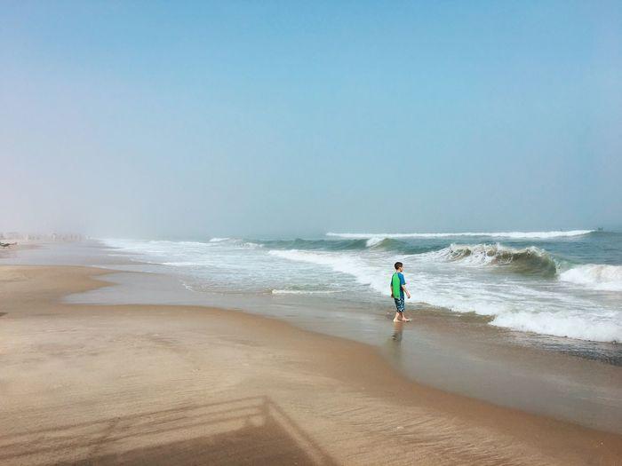 Boy on shore at beach against clear sky