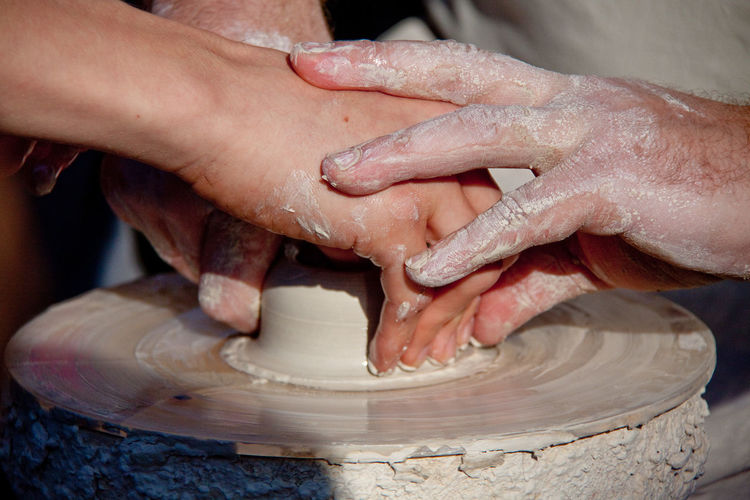 Cropped Image Of People Shaping Clay On Pottery Wheel