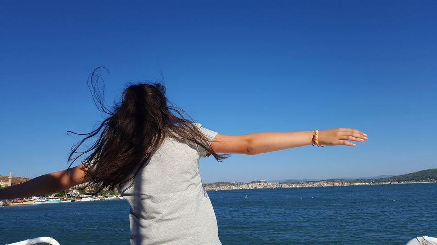 Rear view of woman with arms raised against blue sky