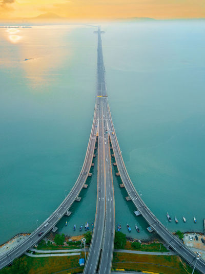 Aerial view of bridge over sea during sunset