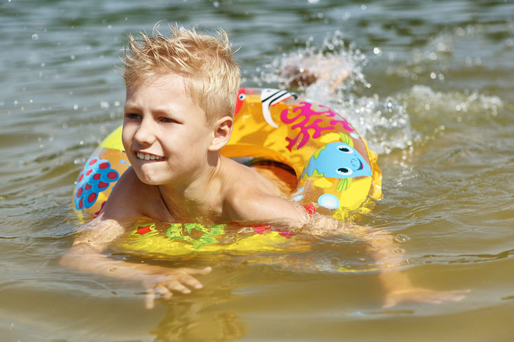 Boy swimming with inflatable ring in lake during sunny day