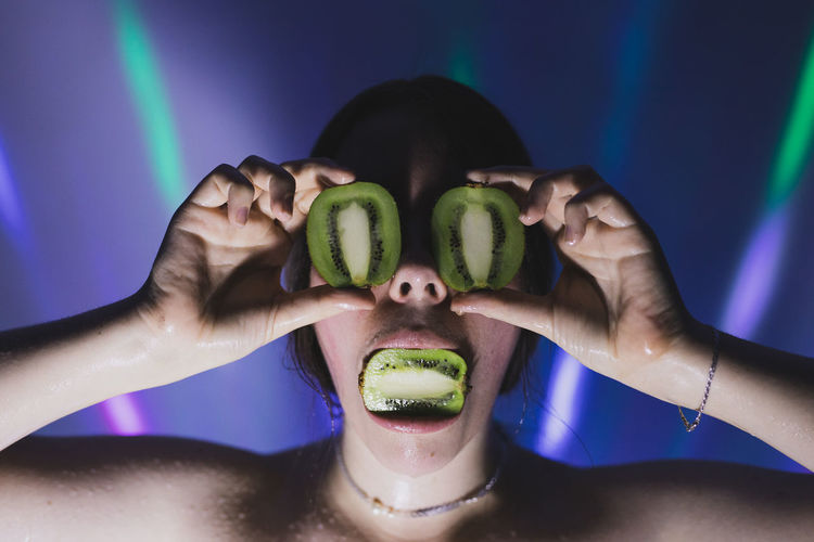 Close-up of woman covering eyes with kiwi slices against lights on wall